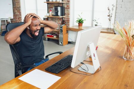 Crazy screaming. Young man, businessman working in office, looking on blank computer screen, monitor. Copyspace for your ad. Finance, business, work, gadgets and tech concept. Freelance, remote worker.