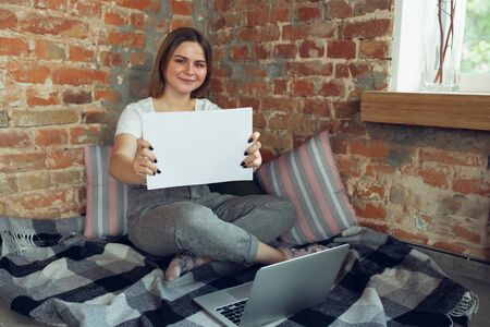 Showing. Young woman working or studying at home, looking on computer screen, monitor. Copyspace for your ad. Finance, business, work, gadgets and tech concept. Freelance, education, remote work.