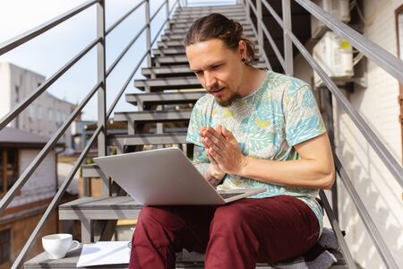 Praying. Young man, businessman working outdoors concentrated, looking on laptop screen, monitor. Copyspace for your ad. Finance, business, work, gadgets and tech concept. Freelance, remote worker.