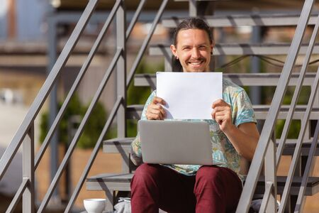 Holding white sheet. Young man, businessman working outdoors, looking on laptop screen, monitor. Copyspace for your ad. Finance, business, work, gadgets and tech concept. Freelance, remote worker.