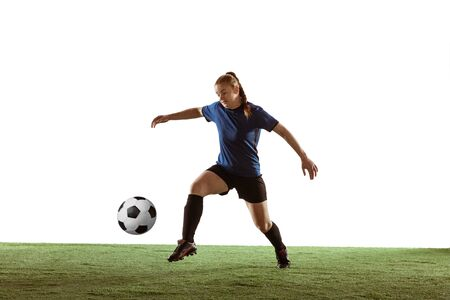 Young female soccer or football player with long hair in sportwear kicking ball for the goal, training on white studio background. Concept of healthy lifestyle, professional sport, motion, movement.