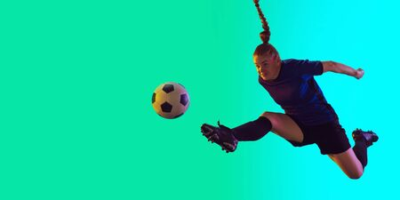 Young female soccer or football player with long hair in sportwear kicking ball for the goal in jump on gradient background, neon. Concept of healthy lifestyle, professional sport, motion, movement.