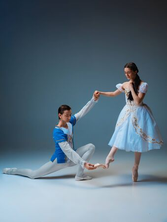 Young and graceful ballet dancers as Cindrella fairytail characters on studio background. Art, motion, action, flexibility, inspiration concept. Flexible caucasian ballet dancers posing, dancing.