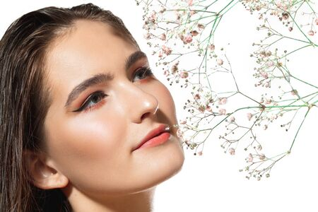 Blooming. Close up of beautiful young woman with tender flowers on white background. Concept of cosmetics, makeup, natural and eco treatment, skin care. Shiny and healthy skin, fashion, healthcare.