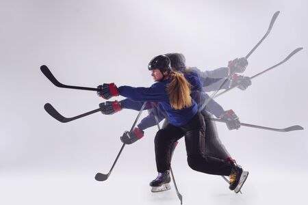 Young female hockey player with the stick on ice court and white background. Sportswoman with equipment training in strobe light. Concept of sport, healthy lifestyle, motion, action, emotions.