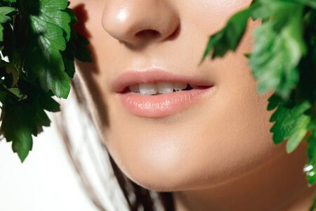 Close up of beautiful female lips with green fresh parsley on white background. Concept of cosmetics, makeup, natural and eco treatment, skin care. Shiny and healthy skin, fashion, healthcare.