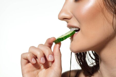 Close up of beautiful female face biting cucumber slice on white background. Concept of cosmetics, makeup, natural and eco treatment, skin care. Shiny and healthy skin, fashion, healthcare. Stock Photo