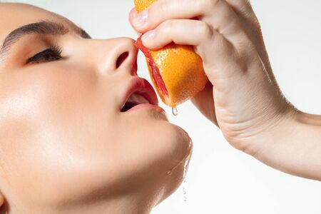 Close up of female lips with grapefruit pouring, splashing juice on white background. Concept of cosmetics, makeup, natural and eco treatment, skin care. Shiny and healthy skin, fashion, healthcare.