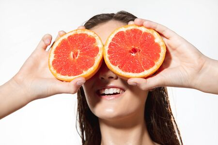 Summer. Close up of beautiful young woman with big grapefruit on white background. Concept of cosmetics, makeup, natural and eco treatment, skin care. Shiny and healthy skin, fashion, healthcare. Stock Photo