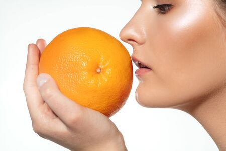 Sun in hands. Close up of beautiful young woman with big grapefruit on white background. Concept of cosmetics, makeup, natural and eco treatment, skin care. Shiny and healthy skin, fashion, healthcare.