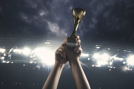 Winner way. Award of victory, male hands tightening the golden cup of winners against cloudy dark sky. Sport, competition, championship, winning, achieving the goal. Prize for success and honor. Stock Photo
