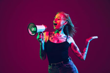 Shouting with megaphone. Young caucasian woman on purple studio background in neon light. Beautiful female model with tattoos. Human emotions, facial expression, sales, ad concept. Freaks culture.