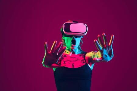Playing with VR-headset. Young caucasian woman on purple studio background in neon light. Beautiful female model with tattoos. Human emotions, facial expression, sales, ad concept. Freak's culture.