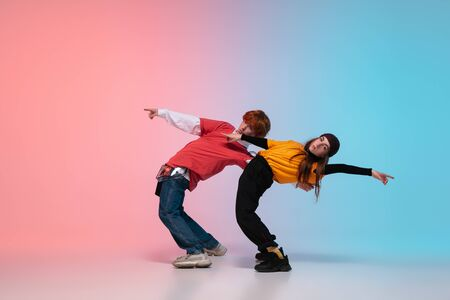 Boy and girl dancing hip-hop in stylish clothes on colorful gradient background at dance hall in neon. Youth culture, movement, style and fashion, action. Fashionable bright portrait. Street dance.