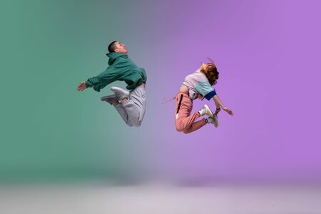 High jump. Boy and girl dancing hip-hop in stylish clothes on colorful gradient background at dance hall in neon. Youth culture, movement, style and fashion, action. Fashionable portrait. Street dance.