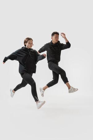Running to freedom. Trendy fashionable couple isolated on white studio background. Stylish woman and man posing in basic minimal clothes equally suitable for both. Concept of equality, inclusive.