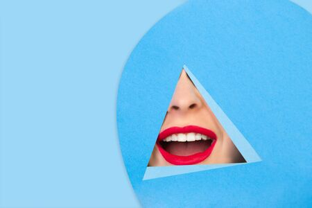 Wow. Close up female red lips peeks throught triangle in blue background. Trendy geometrical style, copyspace. Vibrant colors. Hidden emotion, make up. Sales, proposal, finance and business concept.