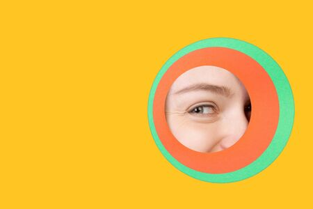 Smiling. Close up female eye peeks throught circle in yellow background. Trendy geometrical style, copyspace. Vibrant colors. Emotion, make up. Sales, proposal, finance and business, fashion concept. Stock Photo