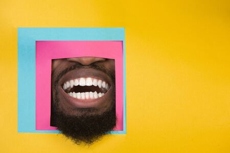 Smile. Mouth of emotional african-american man peeks throught square in yellow background. Trendy geometrical style, copyspace. Vibrant colors. Sales, proposal, finance and business concept. Framing. Banque d'images