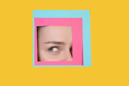 Thoughtful. Face of emotional caucasian woman peeks throught square in yellow background. Trendy geometrical style, copyspace. Vibrant colors. Sales, confines, finance and business concept. Framing. Banque d'images