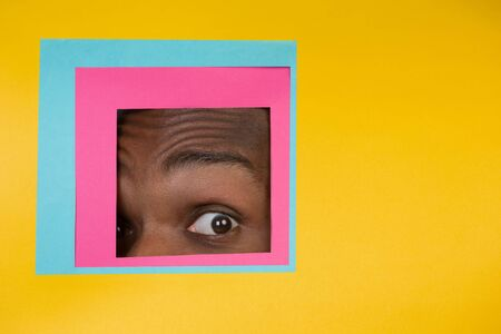 Shocked. Eye of emotional african-american man peeks throught square in yellow background. Trendy geometrical style, copyspace. Vibrant colors. Sales, proposal, finance and business concept.