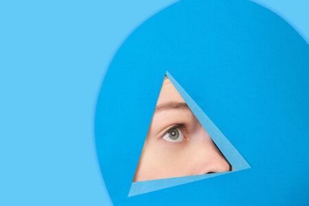 Hopeful. Face of emotional caucasian woman peeks throught triangle in blue background. Trendy geometrical style, copyspace. Vibrant colors. Sales, confines, finance and business concept. Framing. Stok Fotoğraf
