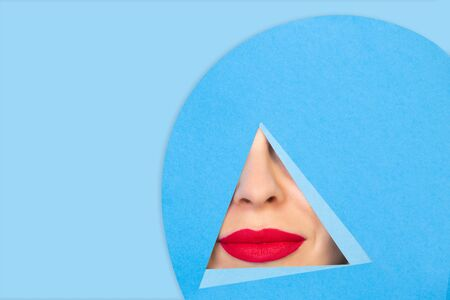 Calm. Close up female red lips peeks throught triangle in blue background. Trendy geometrical style, copyspace. Vibrant colors. Hidden emotion, make up. Sales, proposal, finance and business concept.