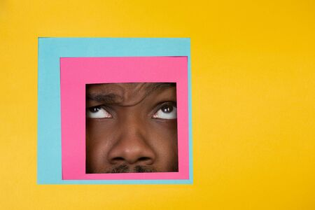 Scared. Face of emotional african-american man peeks throught square in yellow background. Trendy geometrical style, copyspace. Vibrant colors. Sales, confines, finance and business concept. Framing.