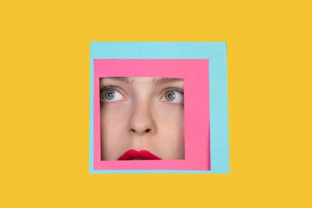 Scared. Face of emotional caucasian woman peeks throught square in yellow background. Trendy geometrical style, copyspace. Vibrant colors. Sales, confines, finance and business concept. Framing.