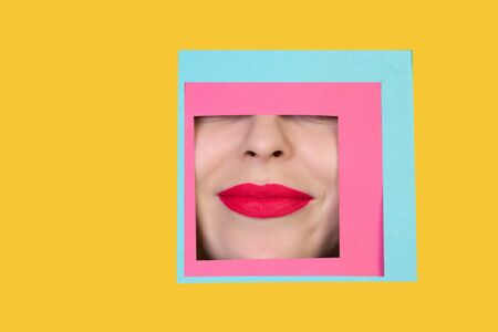 Delighted. Face of emotional caucasian woman peeks throught square in yellow background. Trendy geometrical style, copyspace. Vibrant colors. Sales, confines, finance and business concept. Framing.