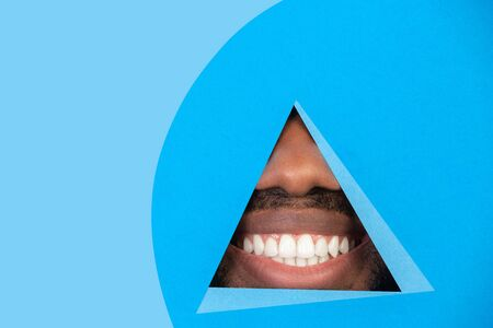 Smiling. Lips of african-american man peeks throught triangle in blue background. Trendy geometrical style, copyspace. Vibrant colors. Sales, proposal, finance and business concept. Looking at side.