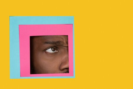 Doubt. Eye of emotional african-american man peeks throught square in yellow background. Trendy geometrical style, copyspace. Vibrant colors. Sales, proposal, finance and business concept. Framing.