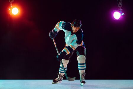 Winner. Male hockey player with the stick on ice court and dark neon colored background. Sportsman wearing equipment, helmet practicing. Concept of sport, healthy lifestyle, motion, wellness, action.