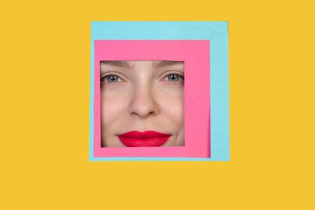 Serious. Face of emotional caucasian woman peeks throught square in yellow background. Trendy geometrical style, copyspace. Vibrant colors. Sales, confines, finance and business concept. Framing.
