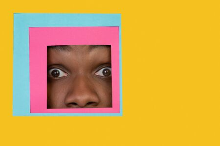 Shocked. Face of emotional african-american man peeks throught square in yellow background. Trendy geometrical style, copyspace. Vibrant colors. Sales, confines, finance and business concept. Framing. Banque d'images