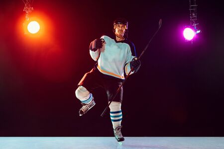 Leader. Male hockey player on ice court and dark neon colored background with flashlights. Sportsman in equipment, helmet practicing. Concept of sport, healthy lifestyle, motion, wellness, action.