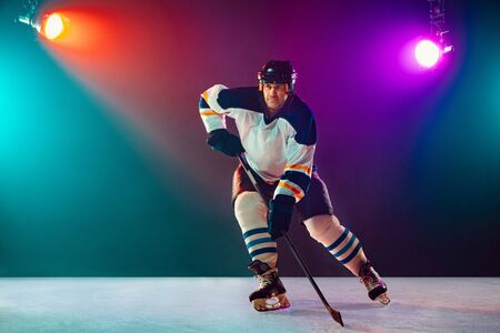Champion. Male hockey player on ice court and dark neon colored background with flashlights. Sportsman in equipment, helmet practicing. Concept of sport, healthy lifestyle, motion, wellness, action. Banque d'images
