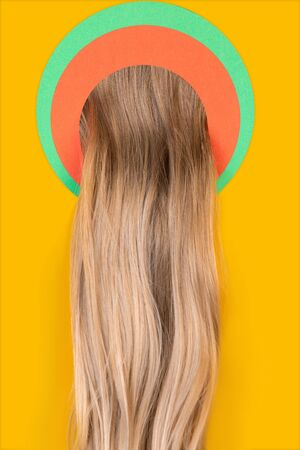 Female long blonde hair peek throught circle in yellow background. Trendy geometrical style, copyspace. Vibrant colors. Sales, proposal, finance and business, fashion concept. Salon treatment.