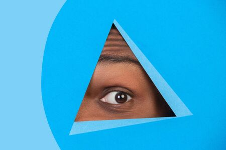 Wondered. Eye of african-american man peeks throught triangle in blue background. Trendy geometrical style, copyspace. Vibrant colors. Sales, proposal, finance and business concept. Looking at side.