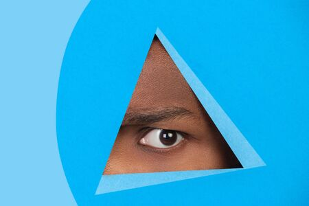 Upset. Eye of african-american man peeks throught triangle in blue background. Trendy geometrical style, copyspace. Vibrant colors. Sales, proposal, finance and business concept. Looking at side. Banque d'images