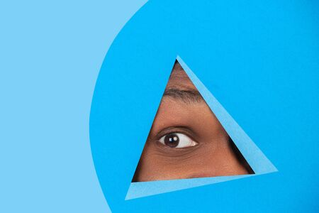 Interested. Eye of african-american man peeks throught triangle in blue background. Trendy geometrical style, copyspace. Vibrant colors. Sales, proposal, finance and business concept. Looking at side. Banque d'images