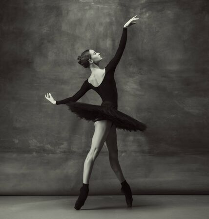 Passioned. Graceful classic ballerina dancing, posing isolated on dark studio background. Elegance black tutu. Grace, movement, action and motion concept. Looks weightless, flexible. Fashionable. Stock Photo