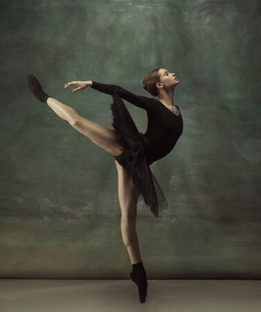 Dancing night. Graceful classic ballerina dancing, posing isolated on dark studio background. Elegance black tutu. Grace, movement, action and motion concept. Looks weightless, flexible. Fashionable. Stock fotó