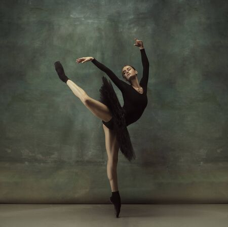 Dancing night. Graceful classic ballerina dancing, posing isolated on dark studio background. Elegance black tutu. Grace, movement, action and motion concept. Looks weightless, flexible. Fashionable.
