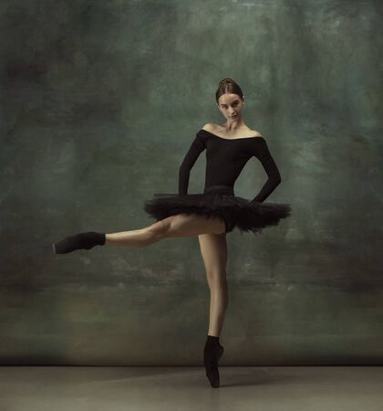 Beautiful portrait. Graceful classic ballerina dancing, posing isolated on dark studio background. Elegance black tutu. Grace, movement, action and motion concept. Looks weightless. Fashionable.