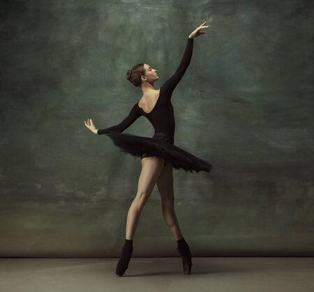 Passioned. Graceful classic ballerina dancing, posing isolated on dark studio background. Elegance black tutu. Grace, movement, action and motion concept. Looks weightless, flexible. Fashionable.
