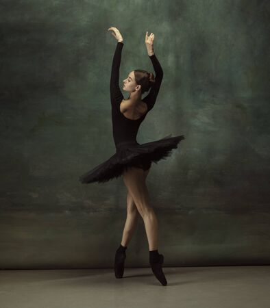 Art motion. Graceful classic ballerina dancing, posing isolated on dark studio background. Elegance black tutu. Grace, movement, action and motion concept. Looks weightless, flexible. Fashionable. Stock fotó