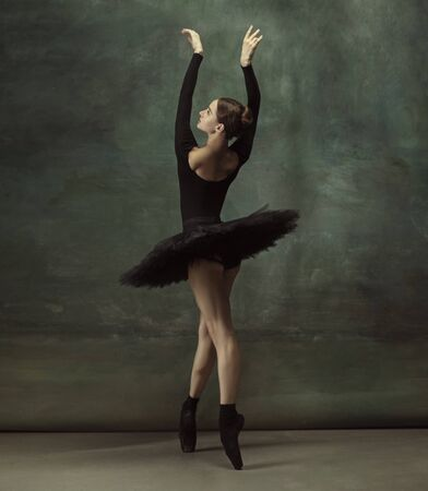 Art motion. Graceful classic ballerina dancing, posing isolated on dark studio background. Elegance black tutu. Grace, movement, action and motion concept. Looks weightless, flexible. Fashionable.