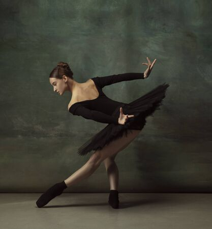 Mystic mood. Graceful classic ballerina dancing, posing isolated on dark studio background. Elegance black tutu. Grace, movement, action and motion concept. Looks weightless, flexible. Fashionable.