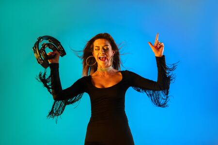 Caucasian female singer with tambourin isolated on blue studio background in neon light. Beautiful female model in black dress. Concept of human emotions, facial expression, ad, music, art, festival.